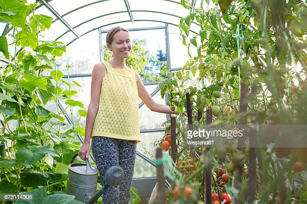 Woman with watering can in a greenhouse