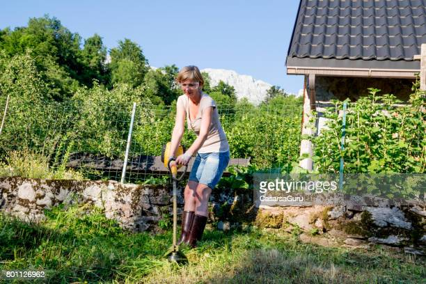 Woman With Weed Trimmer Cutting Grass At The Edge Of The Mountain House