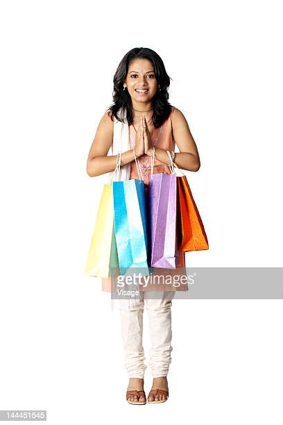 Woman with welcome gesture and shopping bags