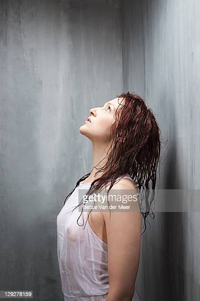 Woman with wet hair and dress looking up.