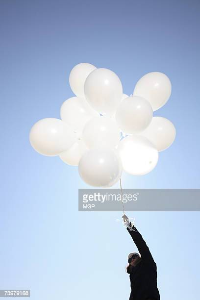 Woman with white balloons, low angle view