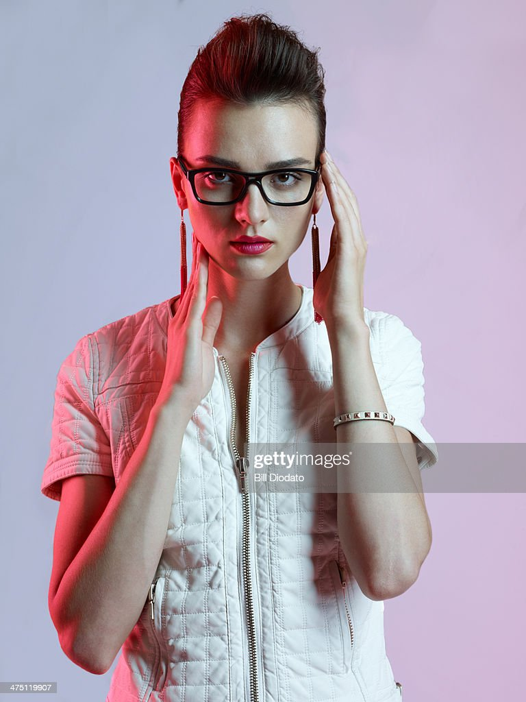 Woman with white leather jacket and black glasses : Stock Photo
