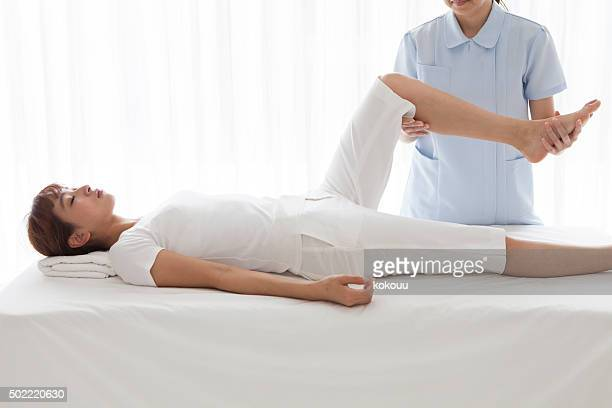 Woman with whom to massage the knee at the salon
