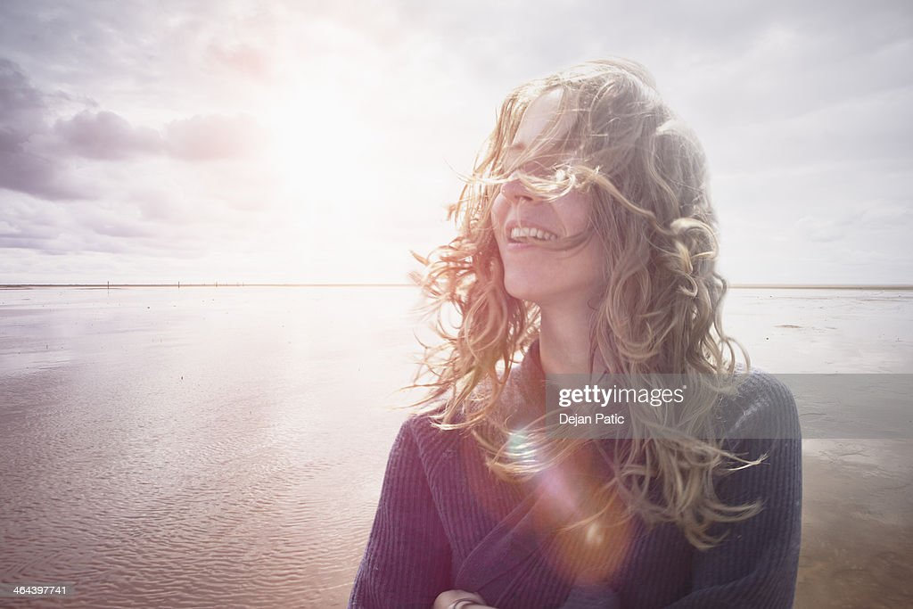 Woman with wind in hair, backlight lens flair