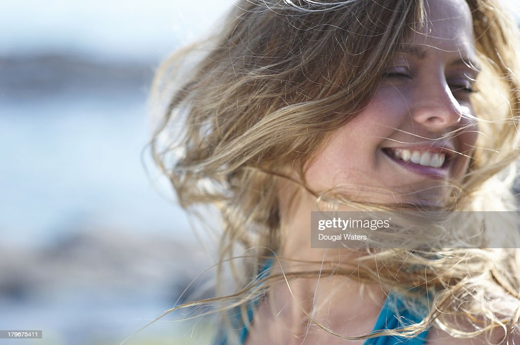 Woman with wind swept hair, smiling. : Stock Photo