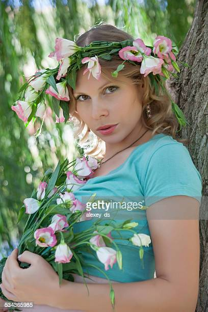 Woman with wreath on head and pink spring flowers
