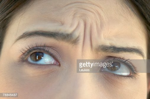Woman with wrinkled brow, high section, close-up of eyes