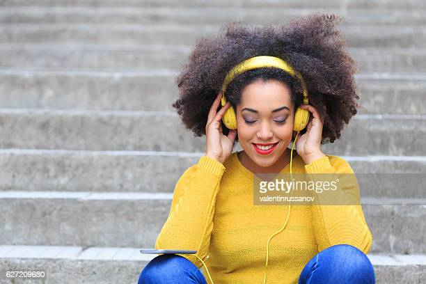 Woman with yellow headphones listening music