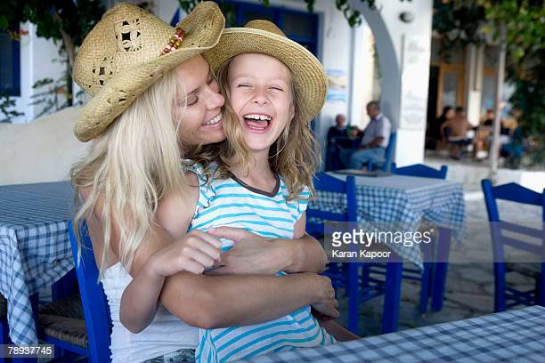 Woman with young girl at an outdoor restaurant smiling.