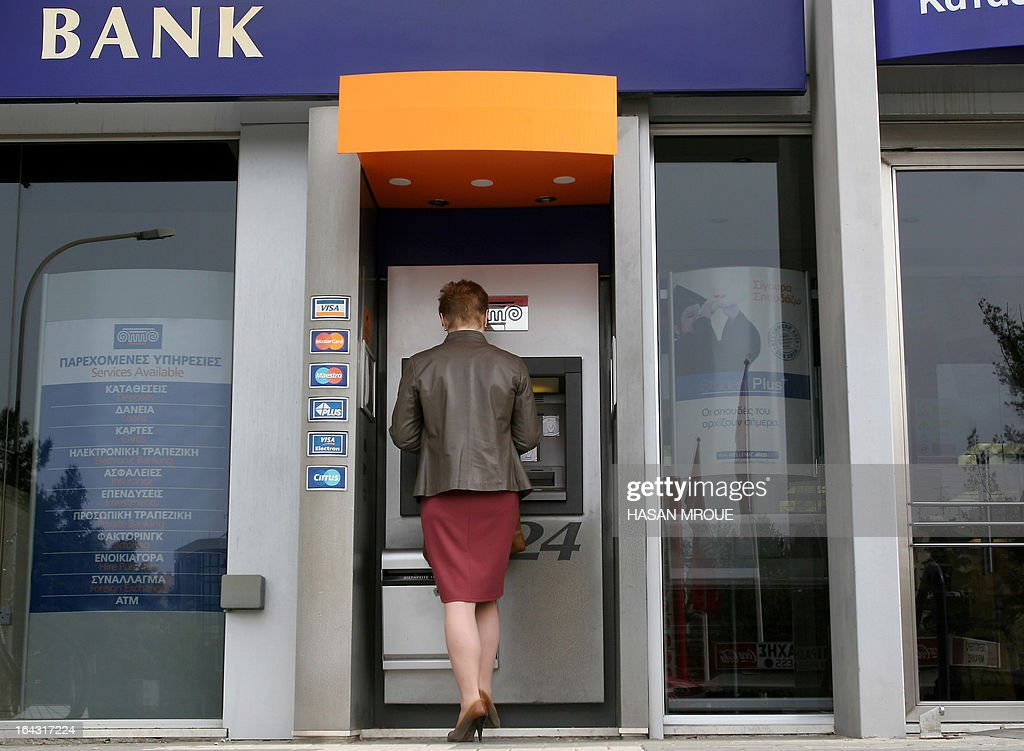 A woman withdraws money from the ATM of a bank in the Cypriot capital Nicosia on March 22, 2013. Cyprus plans a tax of up to 15 percent on bank deposits as part of a deal to secure bailout funds, state television said, after Russia spurned its plea for an economic lifeline to stave off bankruptcy.
