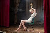 woman woman rolling hair in bun on stage.