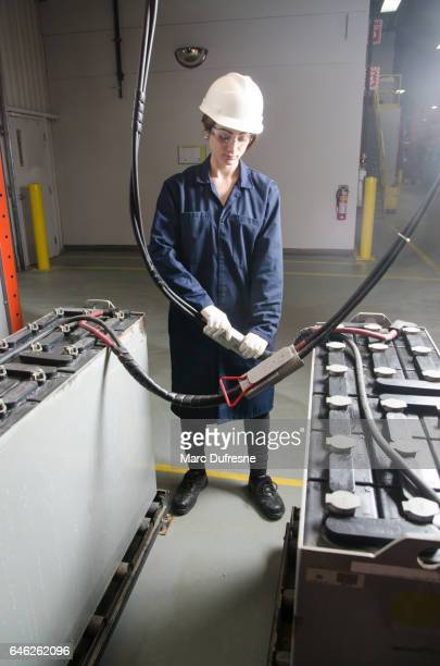 Woman worker connecting huge battery cable with protection gloves