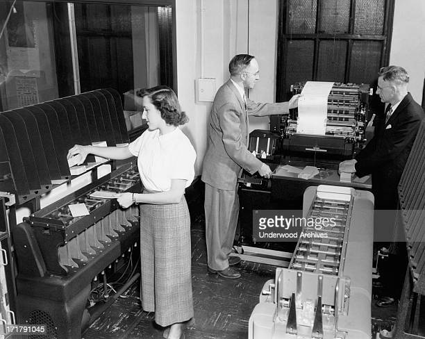 A woman worker loading punch cards and two men viewing a printout from an IBM accounting machine at the Erie Railroad offices Cleveland Ohio February...