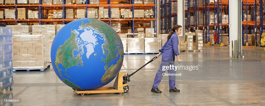 Woman worker pulling large blue ball on hand truck in warehouse : Stock Photo