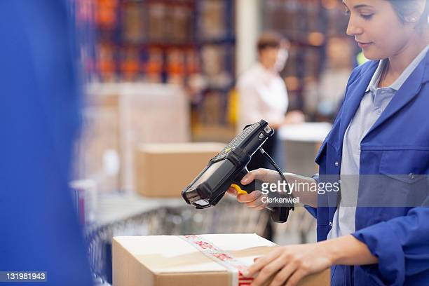 Woman worker scanning cardboard box with bar code reader