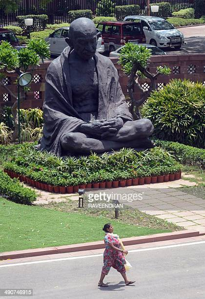 A woman worker walks past the Mahatma Gandhi statue as preparations for the newly elected members of the upcoming 16th Parliament are put in place at...