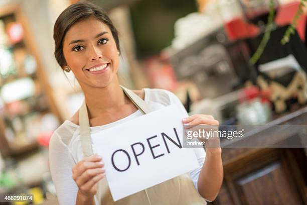 Woman working at a cafe holding sign