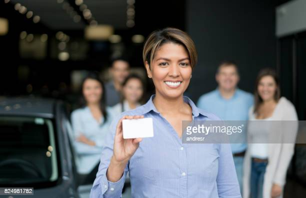 Woman working at a car dealership selling vehicles and holding a business card