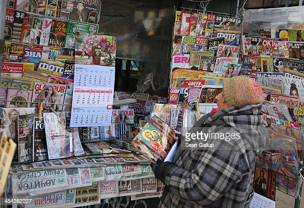 A woman working at a kiosk looks for a place to hang a religious calendar among newspapers and magazines on December 7 2013 in Sofia Bulgaria...