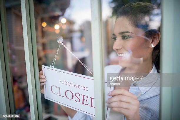 Woman working at a restaurant hanging a closed sign