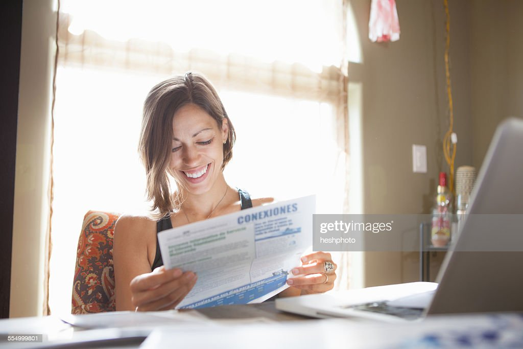 Woman working at desk at home reading paperwork