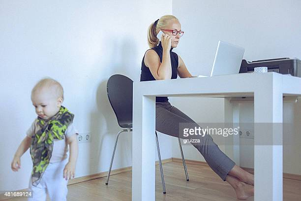 Woman working at home while her baby plays around her