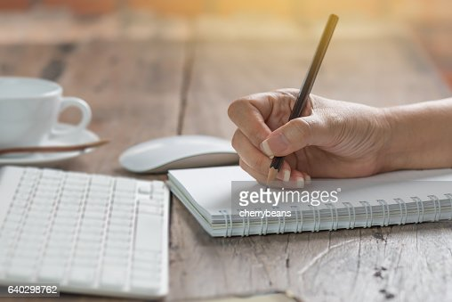 Woman working at old wooden table. : Stock Photo