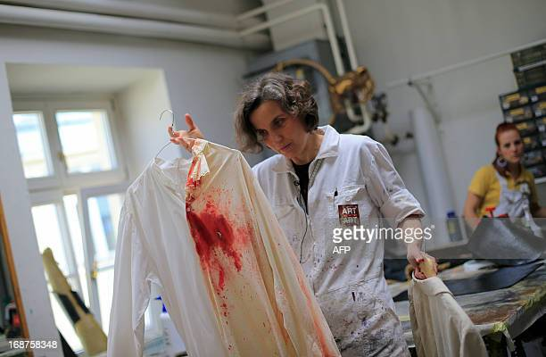 A woman working at the painting atelier for costumes at the 'Art for Art' costume workshop shows a shirt with before and after painting to simulate a...