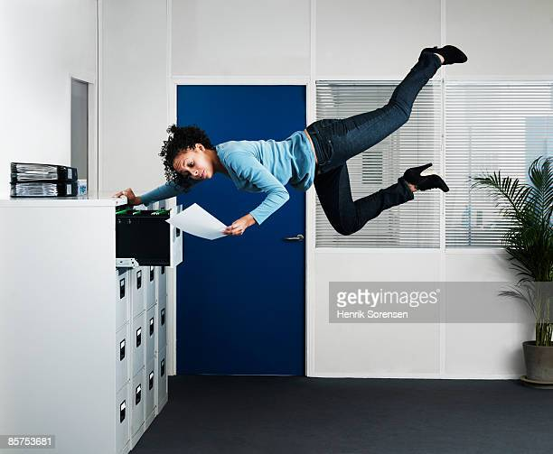 Woman working in  an office floating above the flo