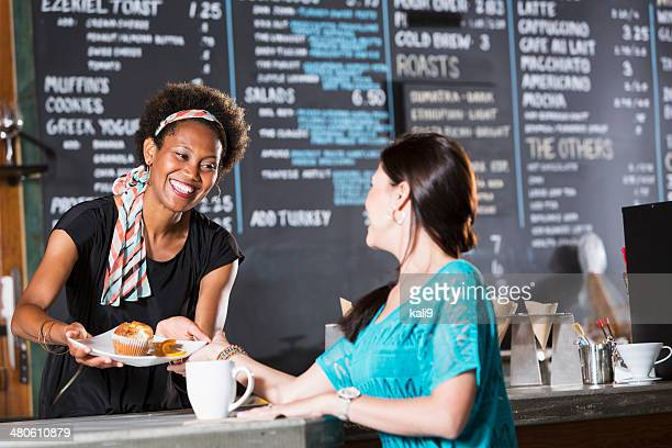 Woman working in coffee shop, serving customer