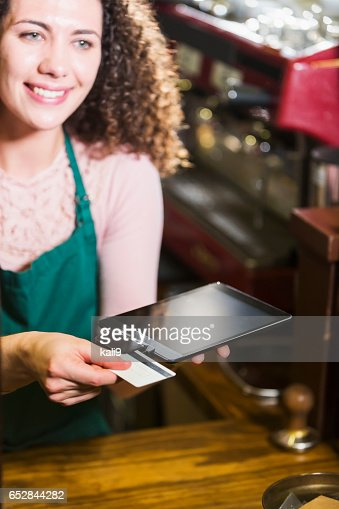 Woman working in coffee shop, using credit card reader : Stock Photo