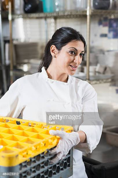 Woman working in commercial kitchen carrying crate