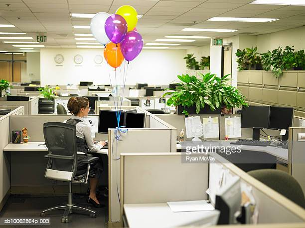 Woman working in cubicle surround by balloons