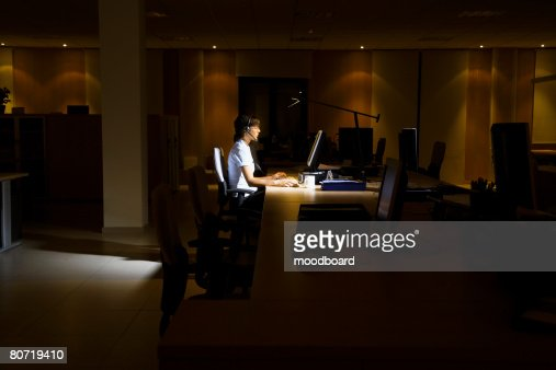Woman Working in Dark Office : Stock Photo