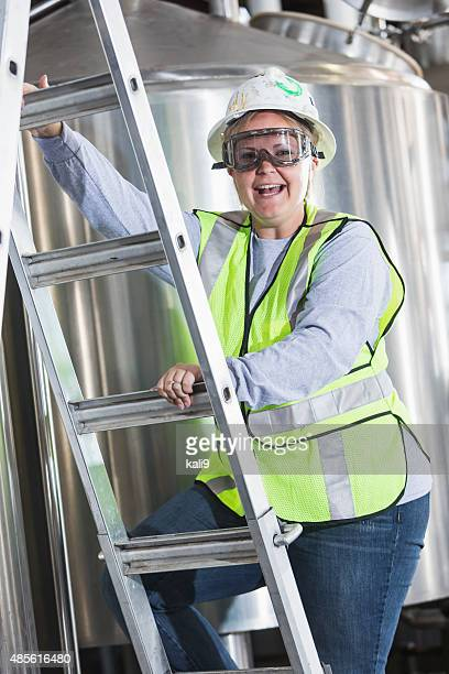 Woman working in factory climbing a ladder