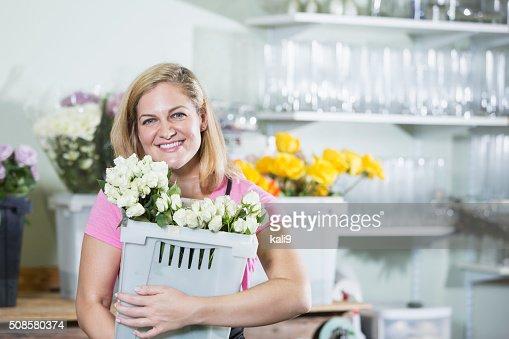 Woman working in flower shop carrying bin : Stock Photo
