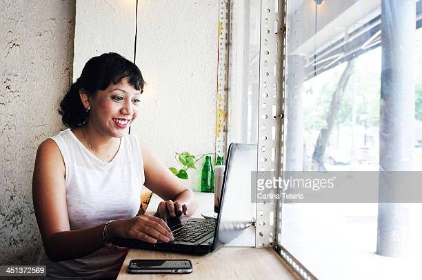 Woman working in front of a coffee shop window