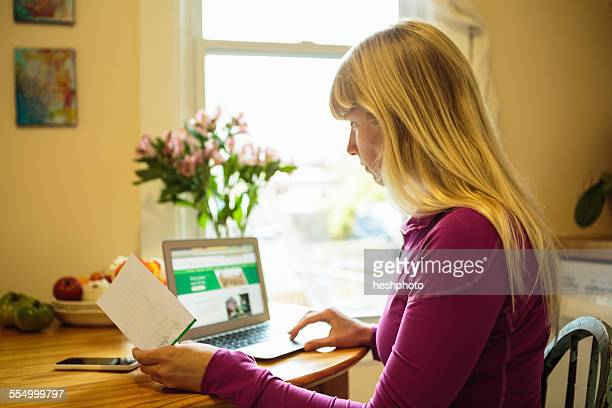 Woman working in kitchen table using laptop and reading instruction booklet