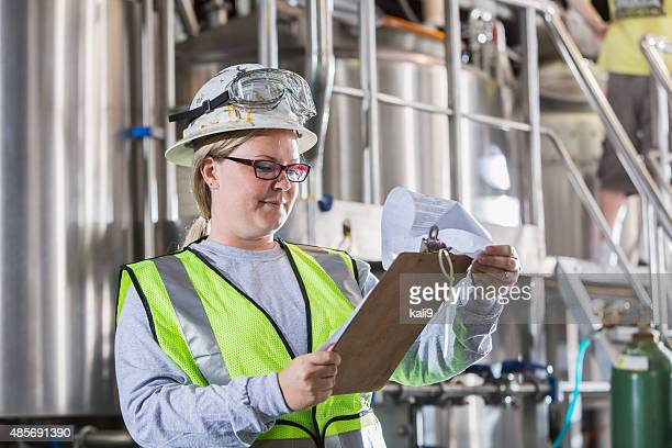 Woman working in manufacturing plant with clipboard