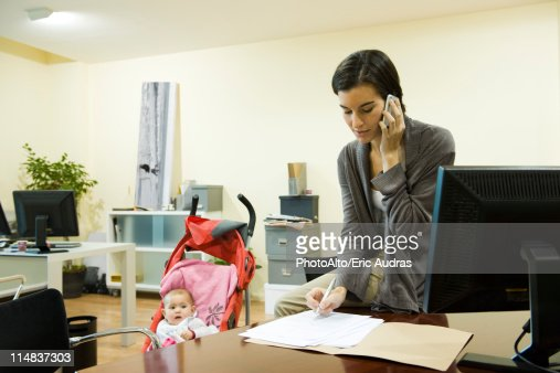 Woman working in office with baby in stroller nearby : Stock Photo