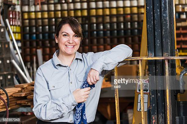 Woman working in printing plant standing by forklift