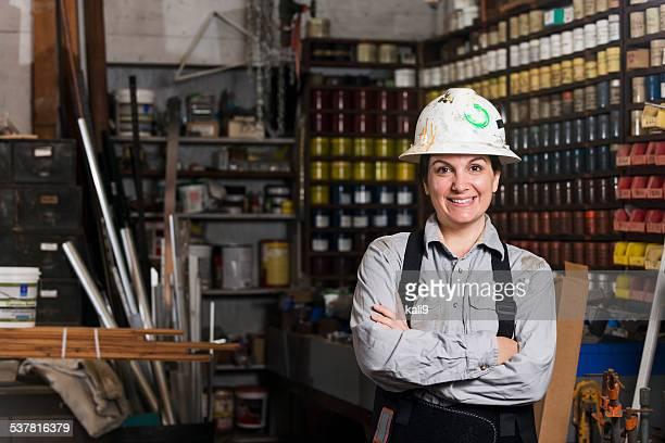 Woman working in printing plant wearing hardhat