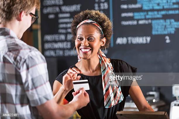 Mulher a trabalhar no restaurante tomar o pagamento do cliente