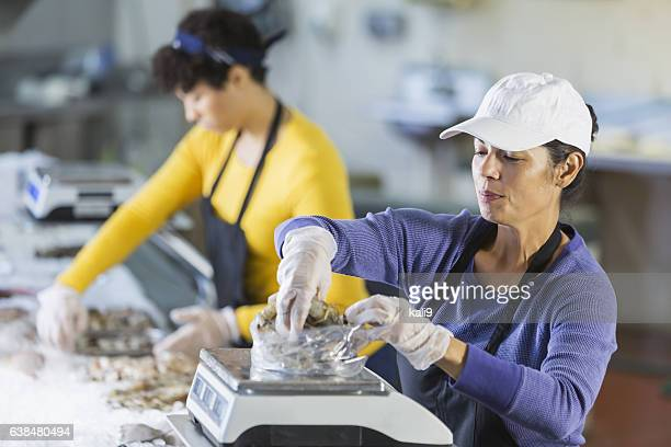 Woman working in seafood market, weighing raw shrimp