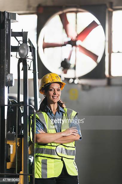 Woman working in warehouse by forklift