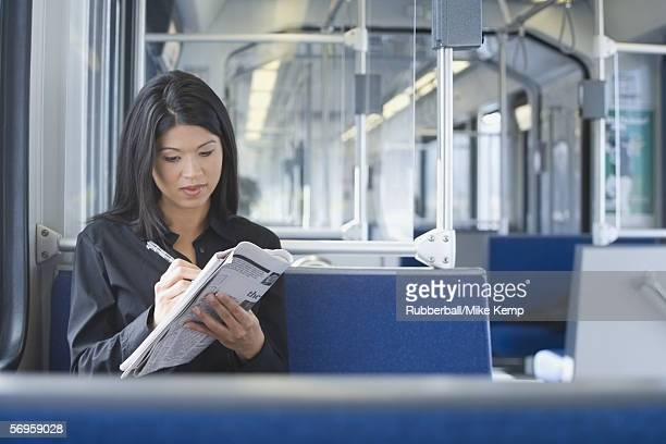 Woman working on a crossword puzzle on a commuter train