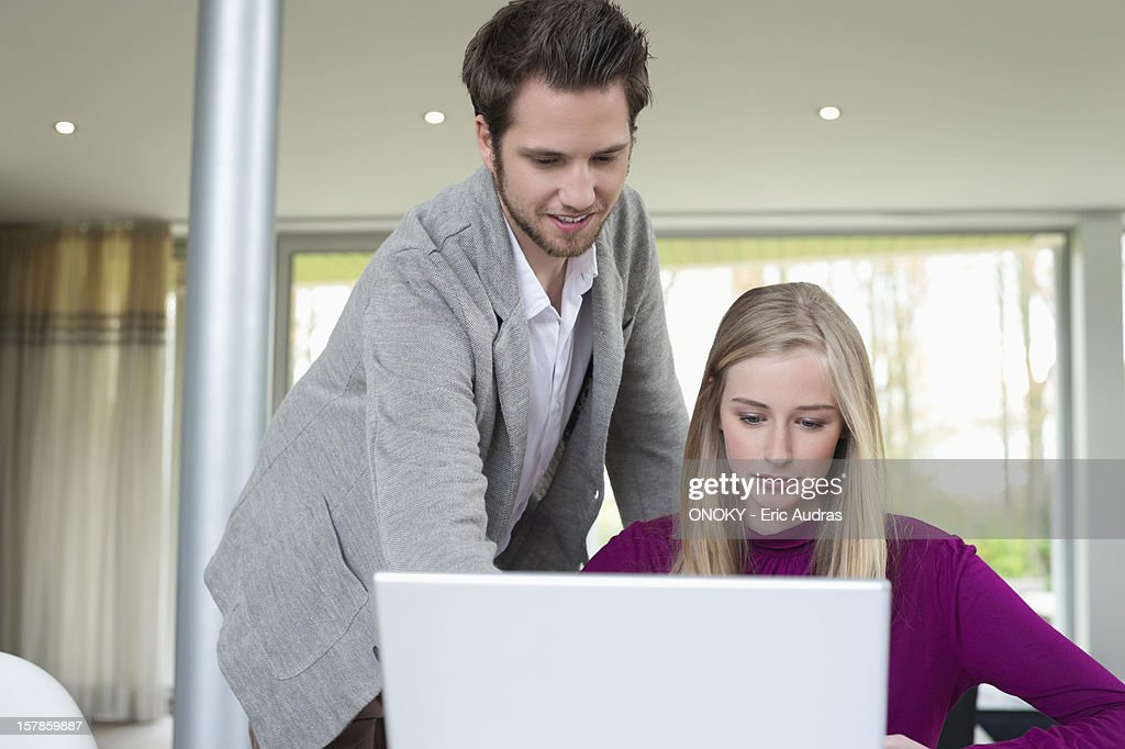 Woman working on a laptop with a man standing beside her : Stock Photo