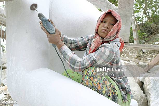 A woman working on a marble Buddha in Sagyin village on 19th May 2016 in Mandalay division Myanmar Sagyin a village 21 miles north of Mandalay is...