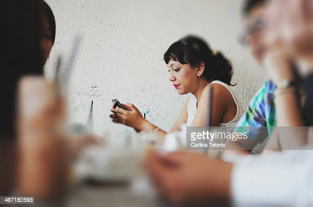 Woman working on a phone in a busy cafe