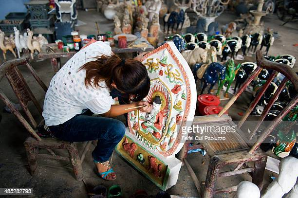 Woman painting a Buddha Statue